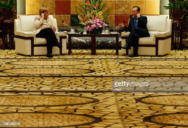 German Chancellor Angela Merkel and Chinese Premier Wen Jiabao adjust their earphones at a meeting with German and Chinese businessmen during their...