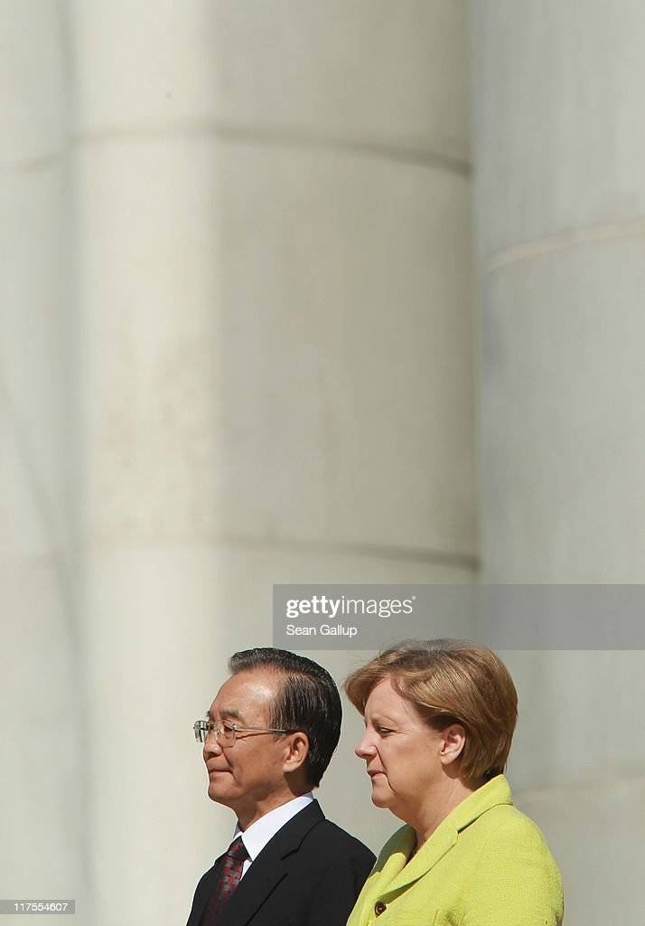 German Chancellor Angela Merkel and Chinese Premier Wen Jiabao listen to their countries' respective national anthems upon Wen's arrival at the Chancellery on June 28, 2011 in Berlin, Germany. The Chinese leader is visiting a variety of European countries and in Germany is participating in the first-ever German-Chinese government consultaitons.