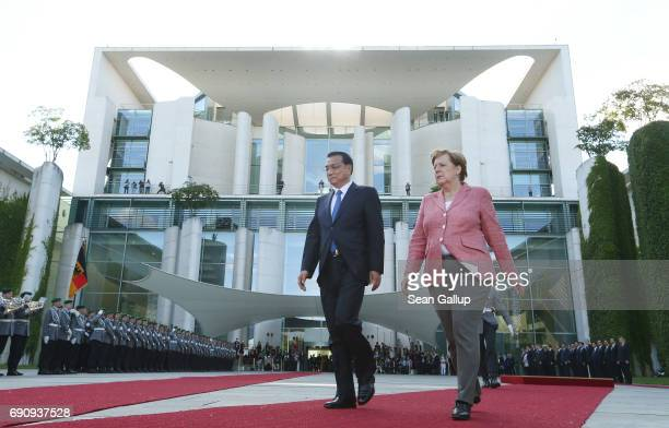 German Chancellor Angela Merkel and Chinese Prime Minister Li Keqiang review a guard of honour upon Li's arrival at the Chancellery on May 31 2017 in...