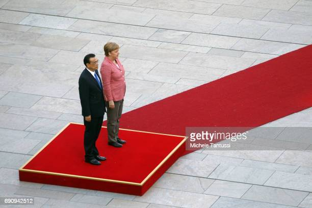 German Chancellor Angela Merkel and Chinese Prime Minister Li Keqiang stand on a podium to listen to the national anthems at the Chancellery on May...