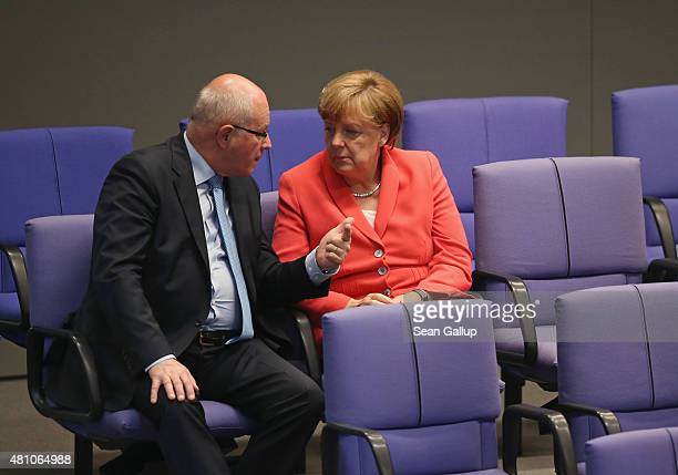German Chancellor Angela Merkel and Christian Democrats Bundestag faction leader Volker Kauder speak with one another during debates prior to votes...