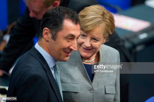 German Chancellor Angela Merkel and coleader of the Green party Cem Ozdemir talk during the first session of the newlyelected parliament on October...