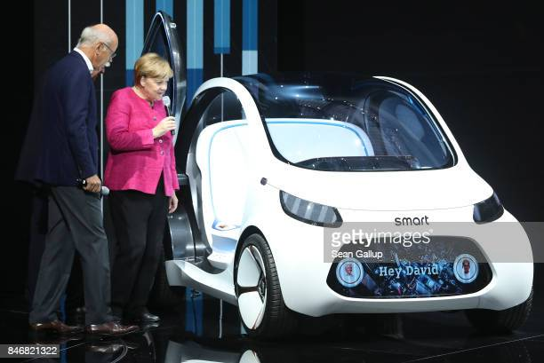 German Chancellor Angela Merkel and Dieter Zetsche Chairman of Daimler AG look at a Smart Vision EQ Fortwo autonomous electric concept car while...