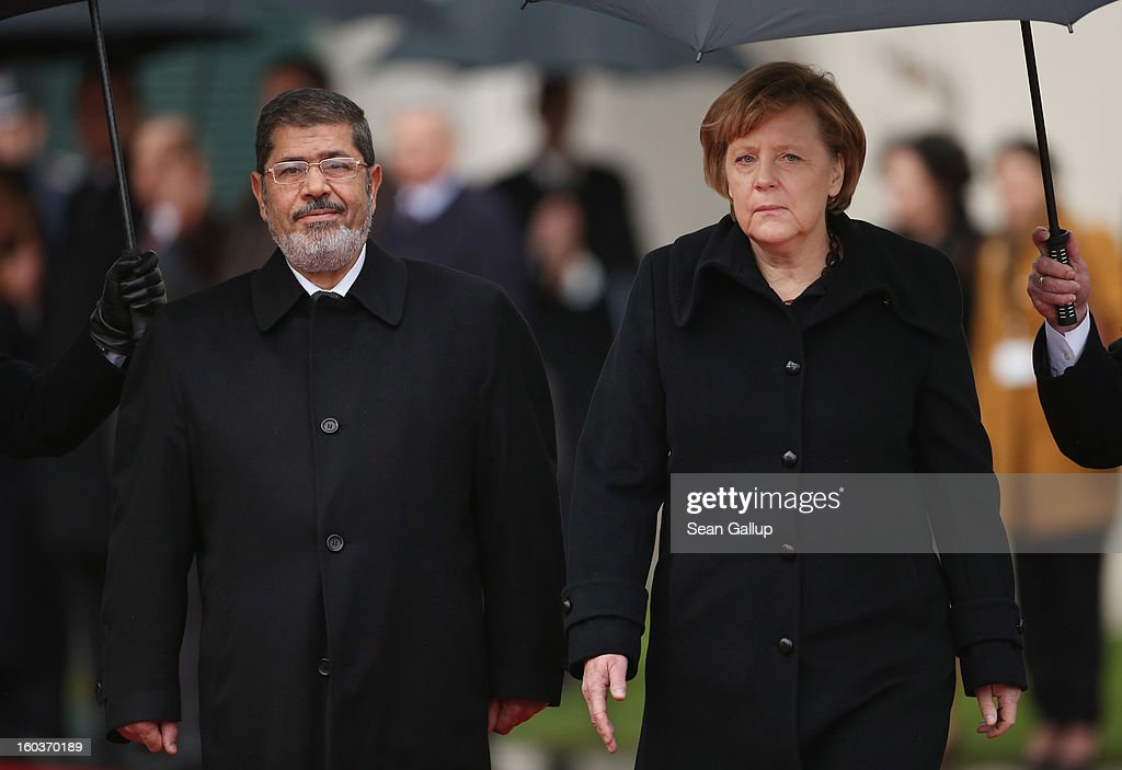 German Chancellor Angela Merkel and Egyptian President Mohamed Mursi review a guard of honour under pouring rain upon Mursi's arrival at the Chancellery on January 30, 2013 in berlin, Germany. Mursi has come to Berlin despite the ongoing violent protests in recent days in cities across Egypt that have left at least 50 people dead. Mursi is in Berlin to seek both political and financial support from Germany.
