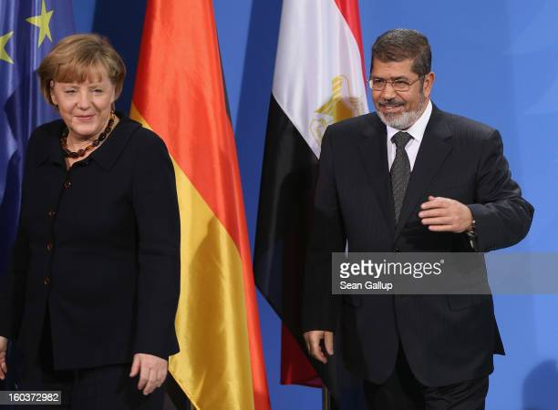 German Chancellor Angela Merkel and Egyptian President Mohamed Mursi depart after speaking to the media following talks at the Chancellery on January...