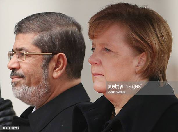 German Chancellor Angela Merkel and Egyptian President Mohamed Mursi listen to their countries' respective national anthems under pouring rain upon...