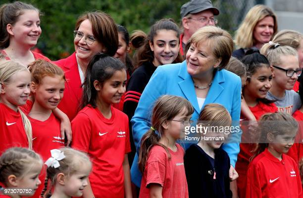 German Chancellor Angela Merkel and Federal Commissioner for Migration Refugees and Integration Annette WidmannMauz pose for a group photo with young...