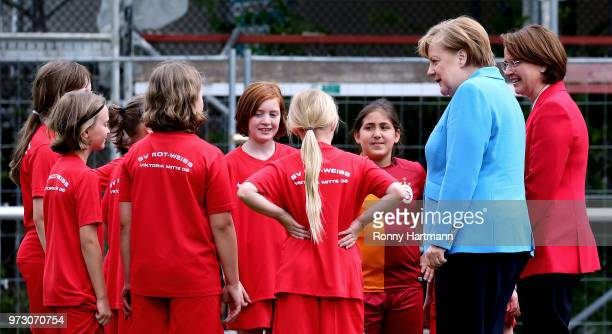 German Chancellor Angela Merkel and Federal Commissioner for Migration Refugees and Integration Annette WidmannMauz chat with young girls during...