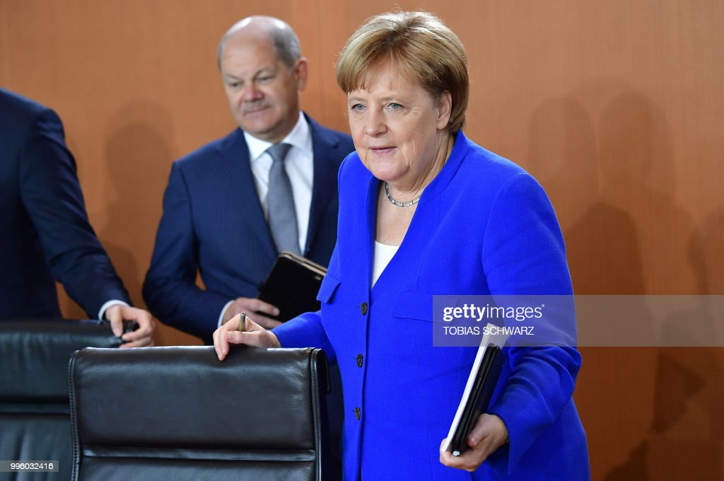German Chancellor Angela Merkel and Finance Minister and Vice-Chancellor Olaf Scholz arrive for the weekly cabinet meeting in Berlin on July 11, 2018.