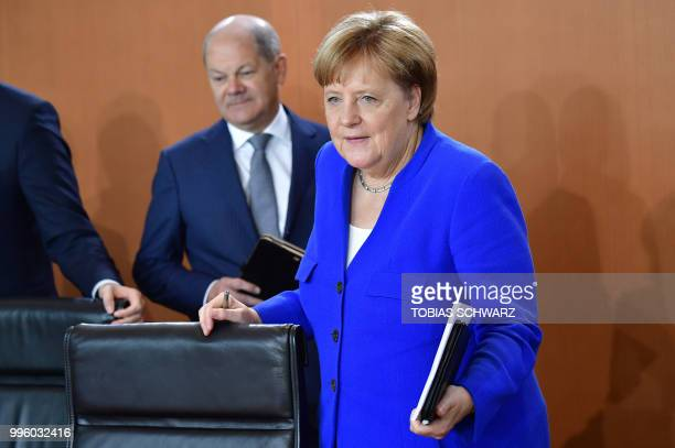 German Chancellor Angela Merkel and Finance Minister and ViceChancellor Olaf Scholz arrive for the weekly cabinet meeting in Berlin on July 11 2018