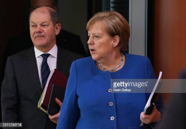 German Chancellor Angela Merkel and Finance Minister and Vice Chancellor Olaf Scholz arrive for the weekly government cabinet meeting on March 11,...