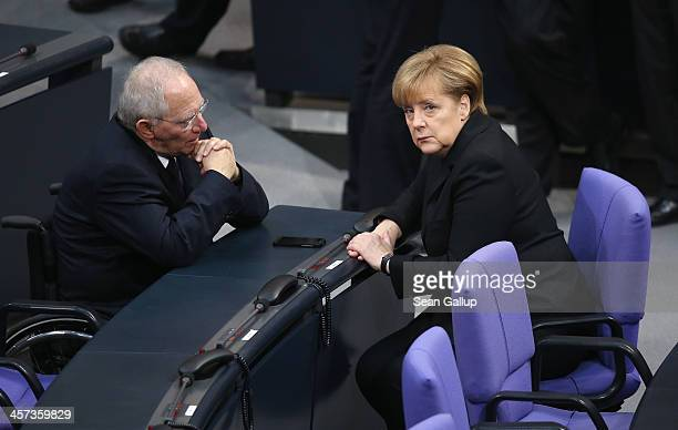 German Chancellor Angela Merkel and Finance Minister Wolfgang Schaeuble chat during a vote at the Bundestag over her third term as chancellor during...