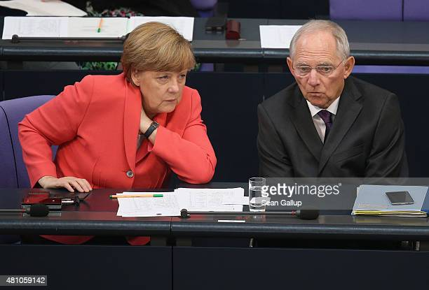 German Chancellor Angela Merkel and Finance Minister Wolfgang Schaeuble speak with one another during debates prior to votes over the third EU...