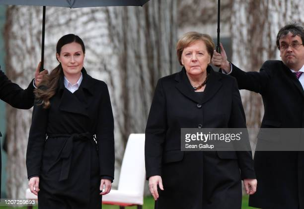German Chancellor Angela Merkel and Finnish Prime Minister Sanna Marin review a guard of honor under umbrellas after listening to their countries'...