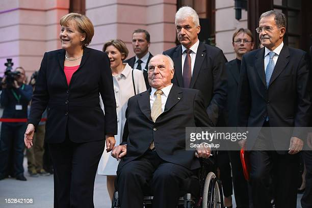 German Chancellor Angela Merkel and former Italian Prime Minister Romano Prodi accompany former German Chancellor Helmut Kohl at his arrival at a...