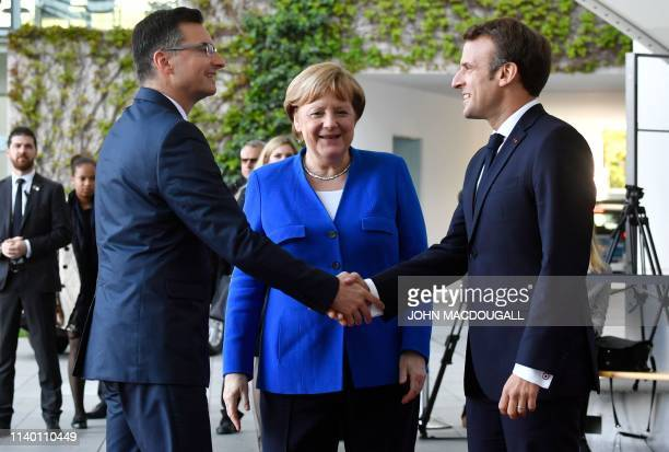 German Chancellor Angela Merkel and French President Emmanuel Macron greet Slovenia's Prime Minister Marjan Sarec as he arives at the chancellery in...