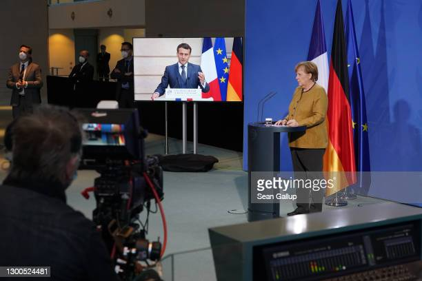 German Chancellor Angela Merkel and French President Emmanuel Macron, who is tuning in from Paris via video link, speak to the media following talks...