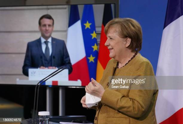 German Chancellor Angela Merkel and French President Emmanuel Macron, who is tuning in from Paris via video link, arrive to speak to the media...