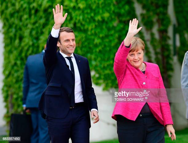 German Chancellor Angela Merkel and French President Emmanuel Macron wave as they walk together during the welcoming ceremony prior talks on May 15,...