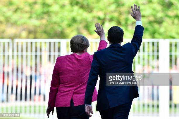 German Chancellor Angela Merkel and French President Emmanuel Macron wave to the crowds during a welcoming ceremony on May 15, 2017 at the...