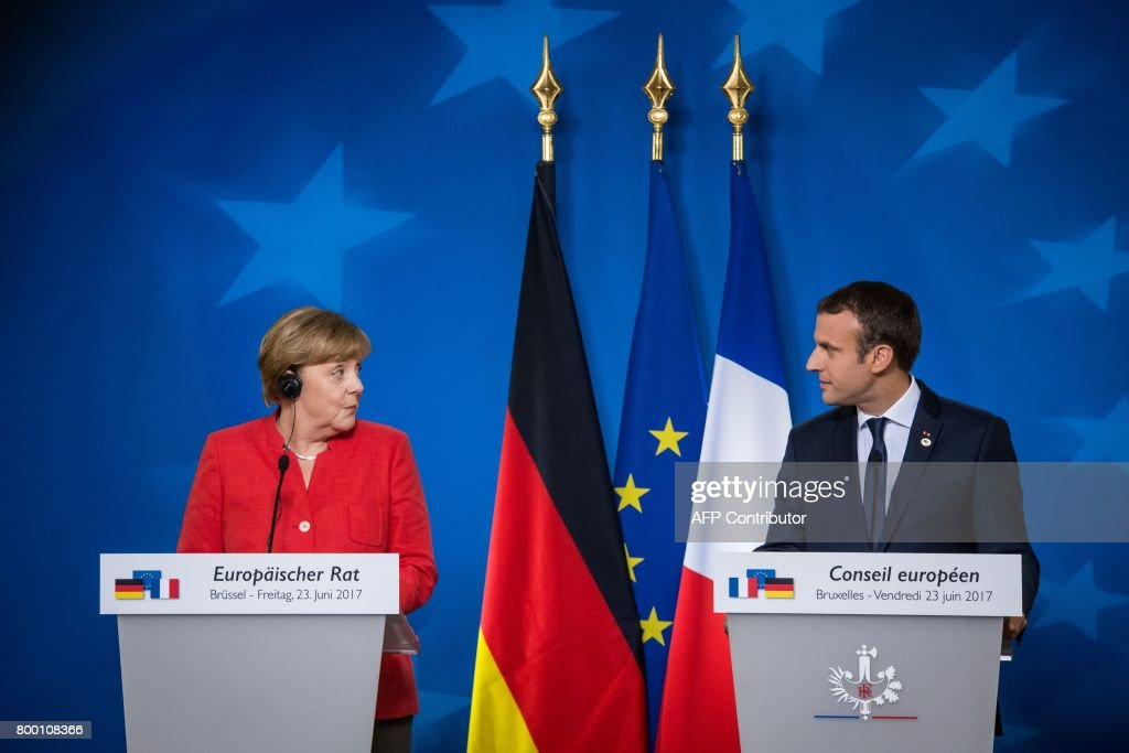 German Chancellor Angela Merkel (L) and French President Emmanuel Macron (R) give a joint press conference following the European Union leaders summit at the European Council, in Brussels, on June 23, 2017. / AFP PHOTO / Aurore Belot