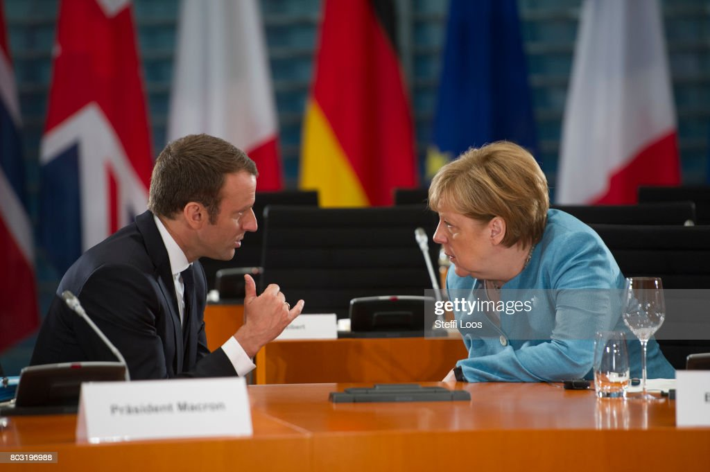 German Chancellor Angela Merkel and French President Emmanuel Macron talk in the conference room during a meeting of EU Leaders before G20 Summit on June 29, 2017 in Berlin, Germany.