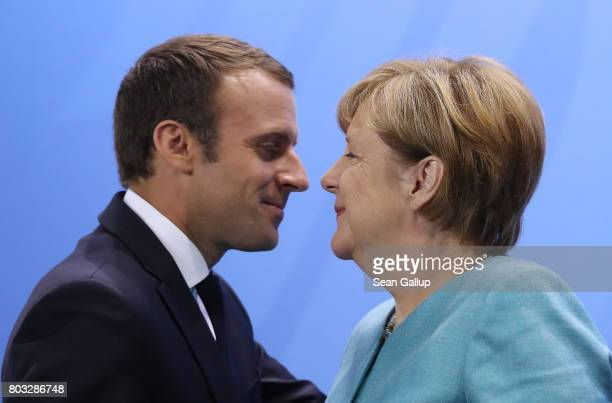 German Chancellor Angela Merkel and French President Emmanuel Macron depart following a meeting of European Union leaders at the Chancellery on June...