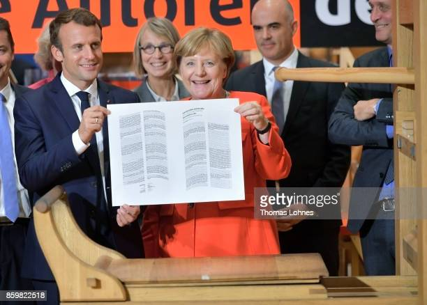 German Chancellor Angela Merkel and French President Emmanuel Macron hold the declaration of the human rights that was printed on an old print press...