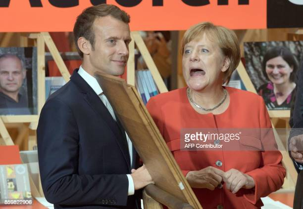 German Chancellor Angela Merkel and French President Emmanuel Macron look at the print of the declaration of Human Rights on a replica of the...