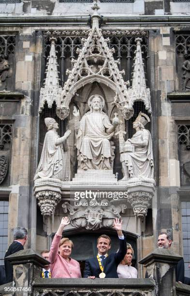 German Chancellor Angela Merkel and French President Emmanuel Macron wave from the balcony of the town hall of Aachen after Macron recieved the...