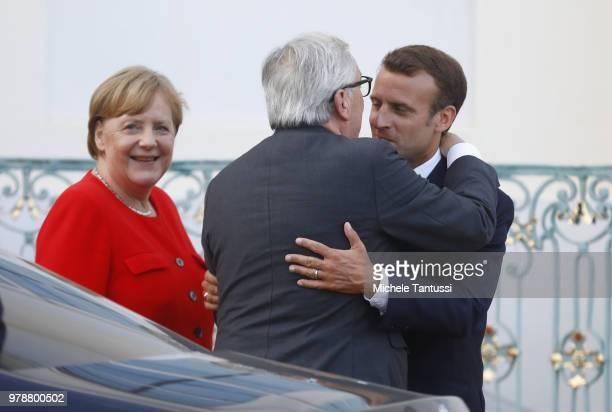 German Chancellor Angela Merkel and French President Emmanuel Macron greet EU commission president Jean-Claude Juncker at Schloss Meseberg...
