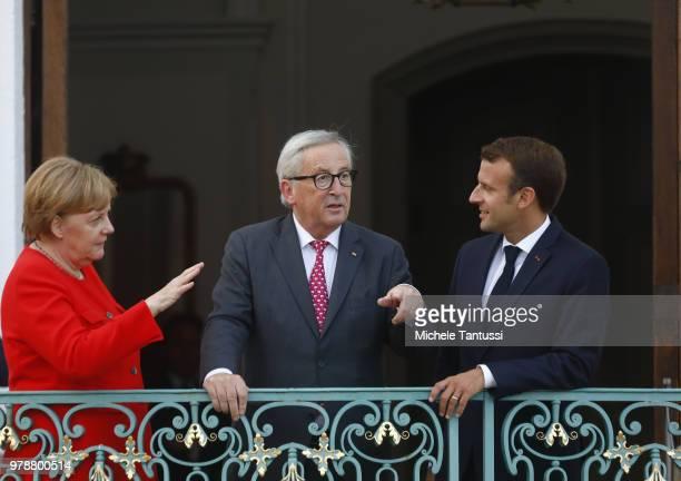 German Chancellor Angela Merkel and French President Emmanuel Macron greet EU commission president JeanClaude Juncker at Schloss Meseberg...