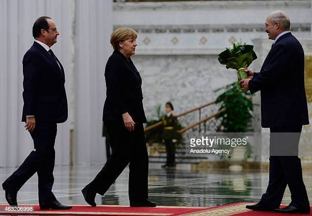 German Chancellor Angela Merkel and French President Francois Hollande are welcomed by Belarus President Alexander Lukashenko ahead of the peace...