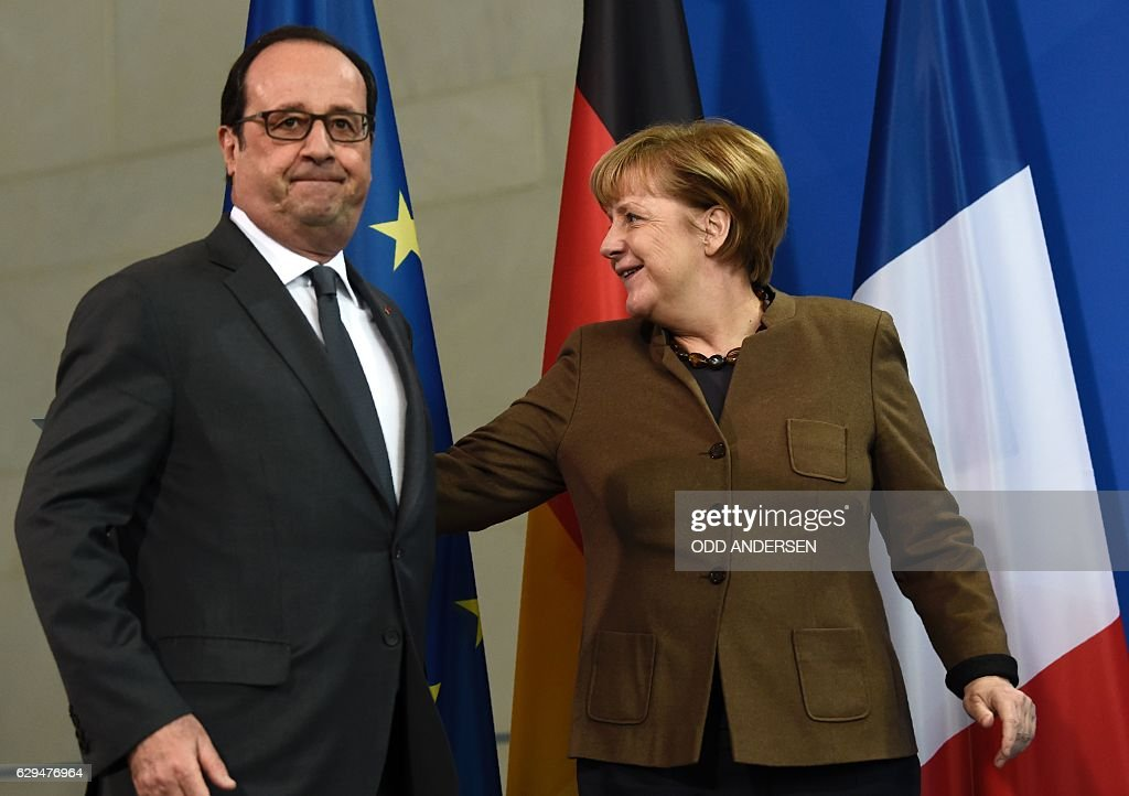German Chancellor Angela Merkel and French President Francois Hollande are pictured in front of the French, the German and the European flags during a joint press conference on December 13, 2016 at the Chancellery in Berlin. / AFP / ODD