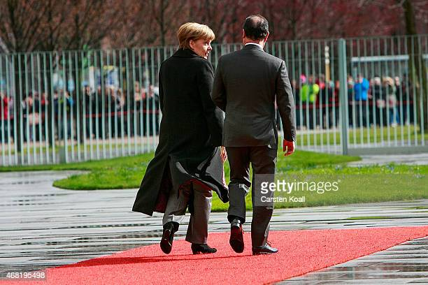 German Chancellor Angela Merkel and French President Francois Hollande attend to review a guard of honour upon Hollande's arrival at the Chancellery...