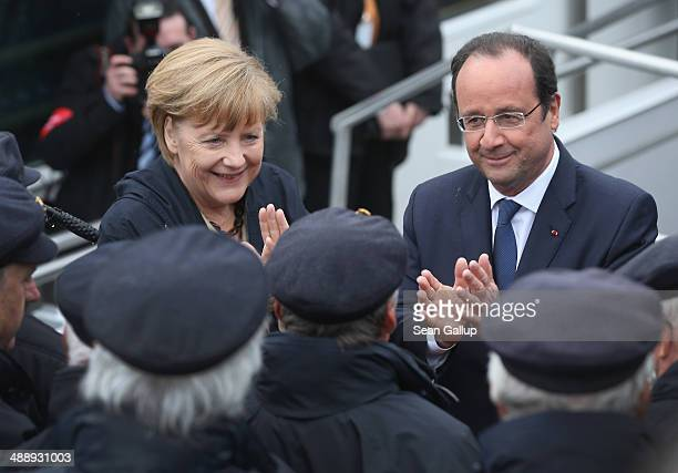German Chancellor Angela Merkel and French President Francois Hollande greet a sailors' choir before boarding a boat to tour the nearby chalk cliffs...