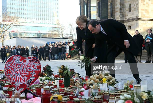 German Chancellor Angela Merkel and French President Francois Hollande lay down flowers at a memorial of flowers and candles for the victims of the...
