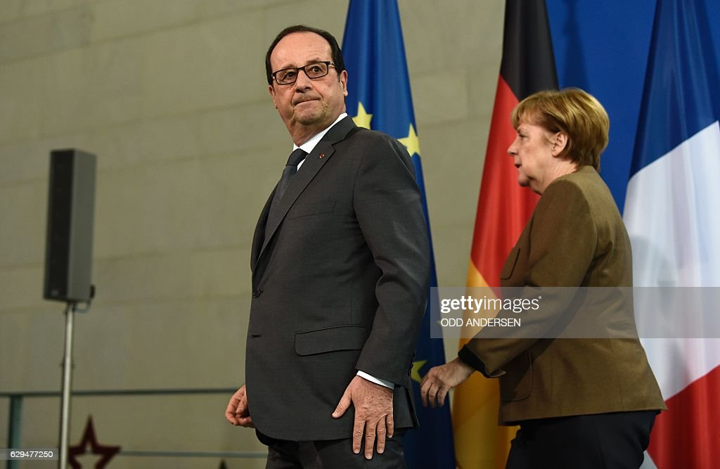 German Chancellor Angela Merkel and French President Francois Hollande leave after a joint press conference on December 13, 2016 at the Chancellery in Berlin. / AFP / ODD