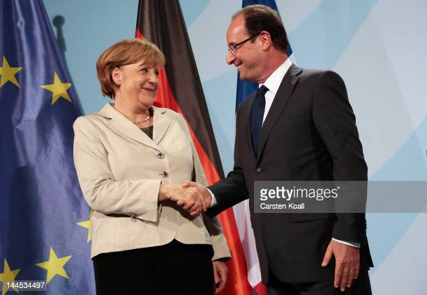 German Chancellor Angela Merkel and French President Francois Hollande pose for the press after a press conference at the Chancellery hours after...