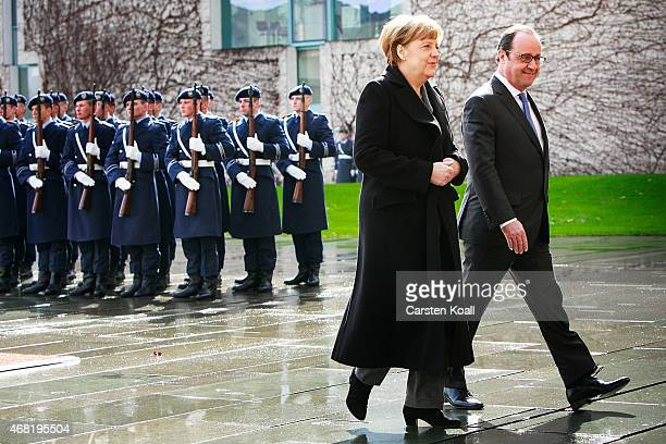 German Chancellor Angela Merkel and French President Francois Hollande review a guard of honour upon Hollande's arrival at the Chancellery on March...