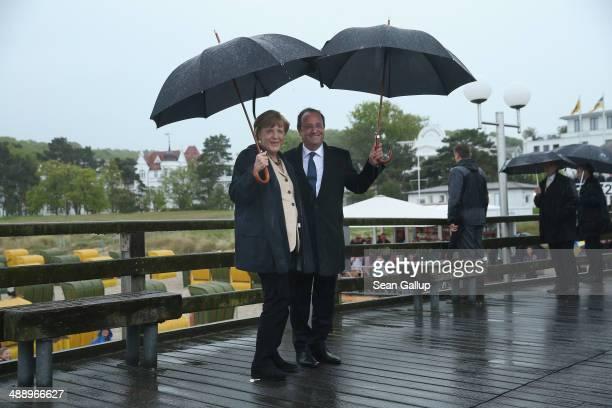 German Chancellor Angela Merkel and French President Francois Hollande walk under umbrellas and rain on a pier on Ruegen Island on May 9, 2014 in...