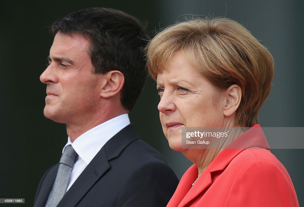 German Chancellor Angela Merkel and French Prime Minister Manuel Valls listen to their countries' national anthems upon Valls's arrival at the Chancellery on September 22, 2014 in Berlin, Germany. Valls is on a two-day visit to Germany at a time when Merkel has been critical of the slow pace of French economic reforms.