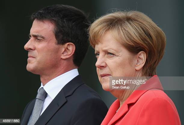 German Chancellor Angela Merkel and French Prime Minister Manuel Valls listen to their countries' national anthems upon Valls's arrival at the...