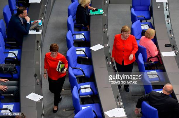 German Chancellor Angela Merkel and German Defence Minister Annegret Kramp-Karrenbauer walk through the rows of the government's bench during a...