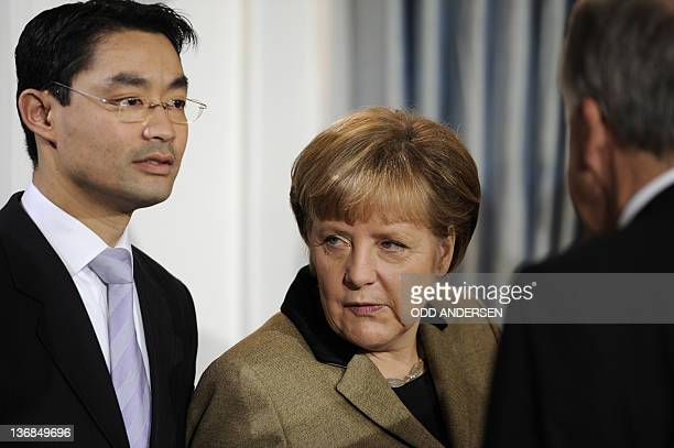 German Chancellor Angela Merkel and German Economy Minister and vice-Chancellor Philipp Roesler pose for pictures during a new year's reception on...
