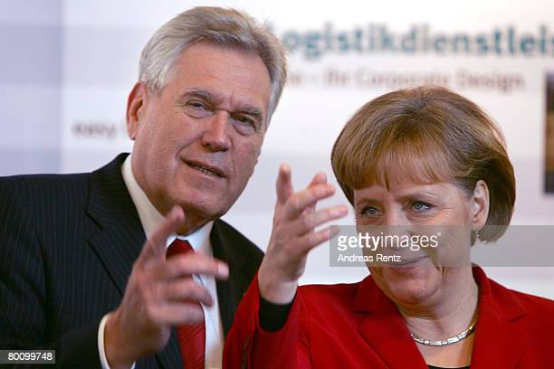 German Chancellor Angela Merkel and German Economy Minister Michael Glos point on at the CeBIT technology fair the first day it opened to the public...