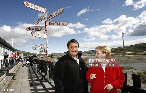 German Chancellor Angela Merkel and German Environment Minister Sigmar Gabriel stand next to a guidepost at the airport of Kangerlussuaq Greenland...