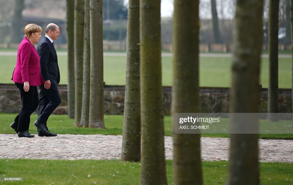 German Chancellor Angela Merkel (L) and German Finance Minister and Vice-Chancellor Olaf Scholz walk on April 11, 2018 at the grounds of Schloss Meseberg castle in Meseberg near Gransee, northeastern Germany, during the second day of a retreat with members of their government to discuss the new coalition government's priorities for the next four years. /