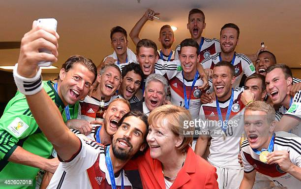 German Chancellor Angela Merkel and German President Joachim Gauck celebrate with the players in the Germany dressing room after the 2014 FIFA World...