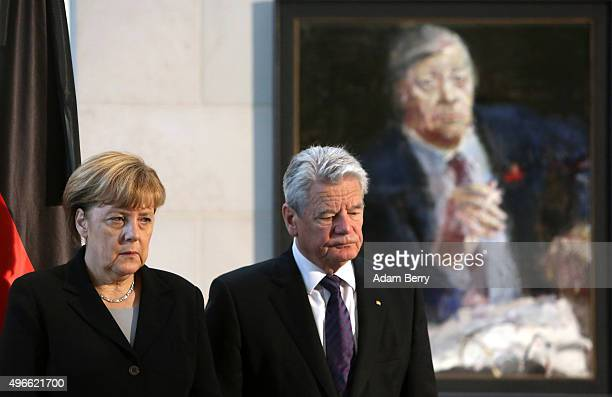 German Chancellor Angela Merkel and German President Joachim Gauck stand in front of a portrait of former German Chancellor Helmut Schmidt following...